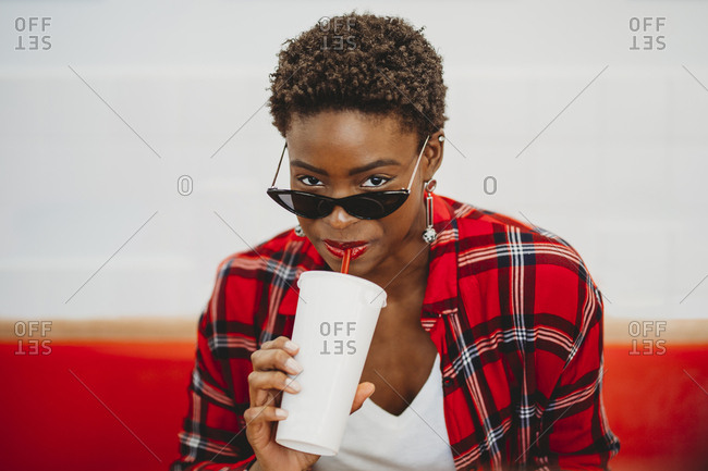 African American woman drinking from plastic cup and sitting at table in cafe