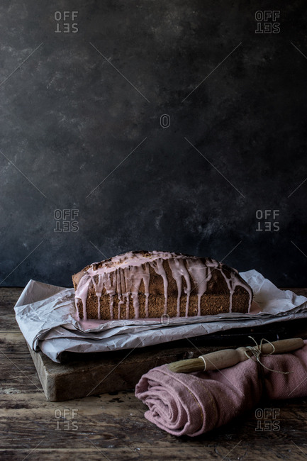 Fresh tasty orange cake with poppy seeds and topping on craft paper on black background