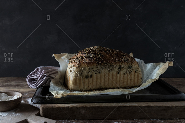 Fresh bread of mother dough with kamut seeds on tray near flour on table on black background
