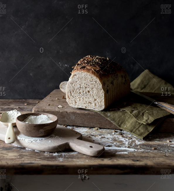 Loaf of delicious rye bread with seeds lying on timber tabletop near raw flour