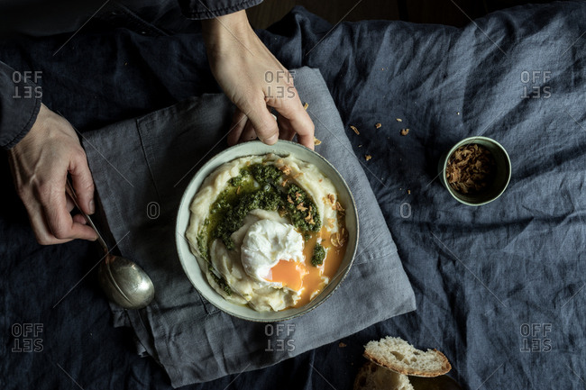 From above crop hands of human holding bowl with cauliflower puree with pesto and eggs on wrinkled blue textile background
