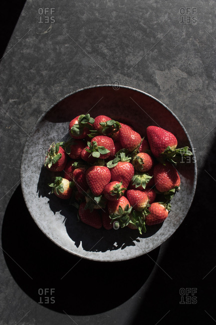 From above pile of fresh strawberry near bowl illuminated by sunbeams in darkness