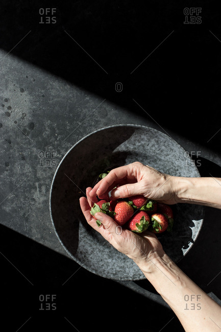 From above crop hands of human holding pile of fresh strawberry near bowl illuminated by sunbeams in darkness