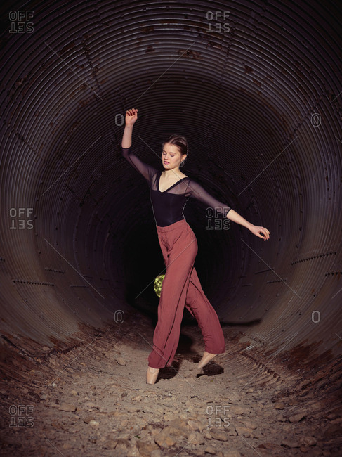 Young ballerina spinning in pipe