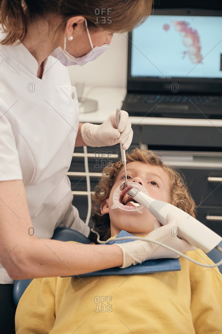 Woman in mask and doctor uniform making scan of teeth of little boy while working in dentist clinic