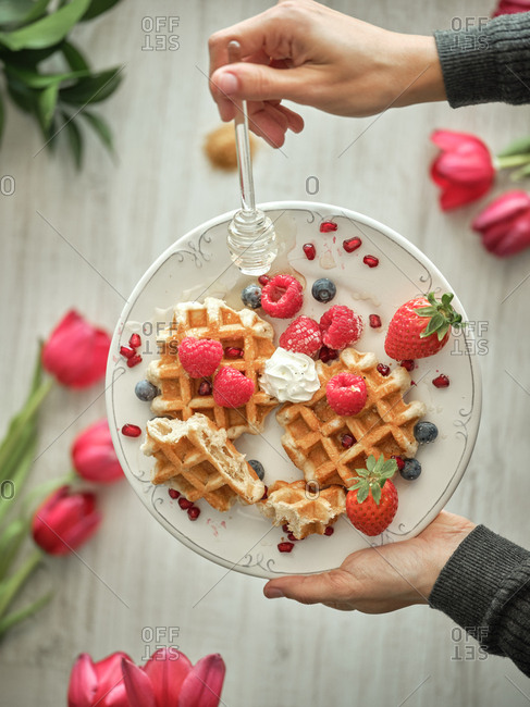 From above crop hands of human holding dish with delicious waffles and fresh berries on blurred background