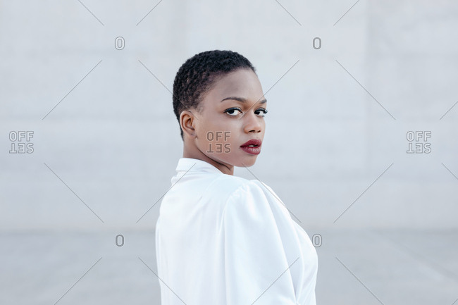 Elegant trendy short haired woman posing and looking at camera near grey construction