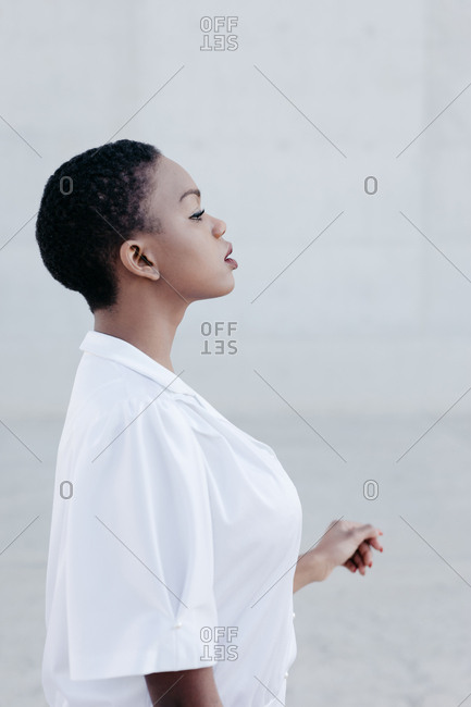 Elegant trendy short haired woman posing and looking away near grey construction