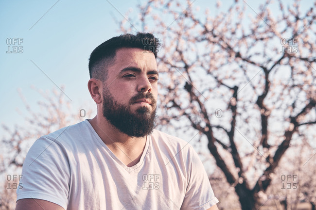 Bearded man meditating in spring garden