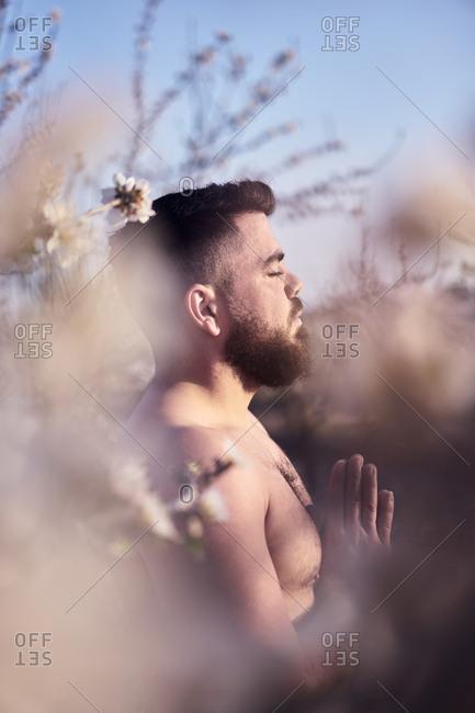 Shirtless man meditating in spring garden
