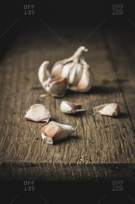 Closeup unpeeled garlic on rough wooden table