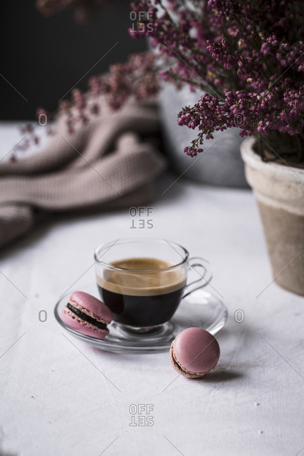 Cup of fresh brewed espresso in glass cup served with pink macaroons on table