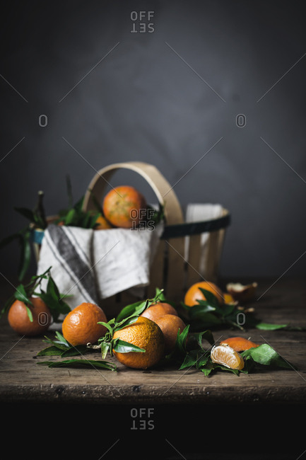 Ripe orange mandarins and basket with towel on rough wooden table