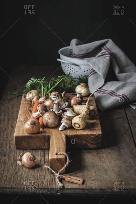 Set of tasty fresh vegetables prepared for cooking on wooden cutting board