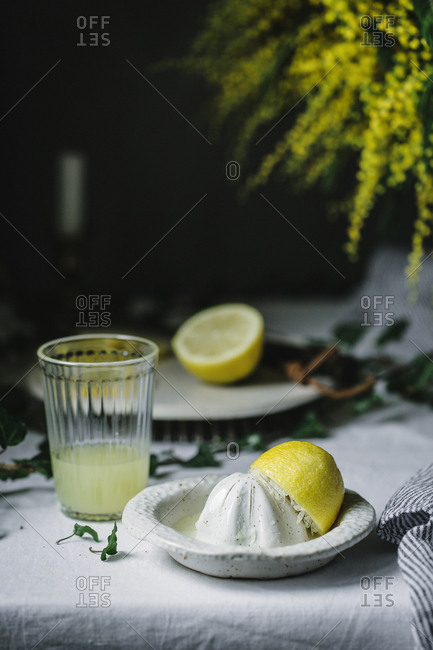 Squeezer and half of lemon at glass with fresh made juice on table