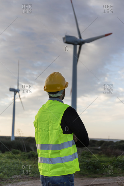 Young engineer looking at wind turbines