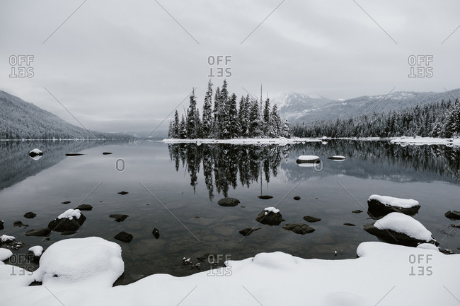 Snowy trees surrounding mountainside lake