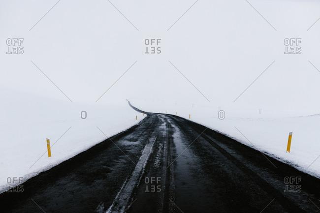 Snow surrounding wet road