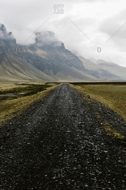 Clouds surround mountains alongside a gravel road