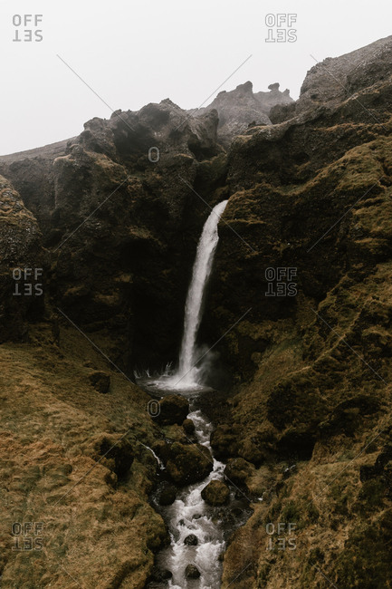 Waterfall flowing down from rocky cliff