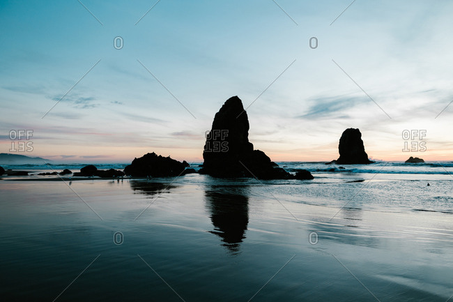 Silhouette of rock formations on a beach at sunset