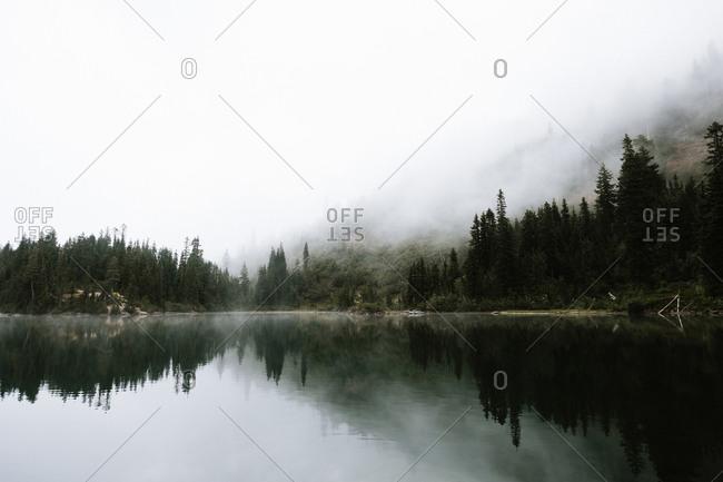 Fog covering lakeside mountain