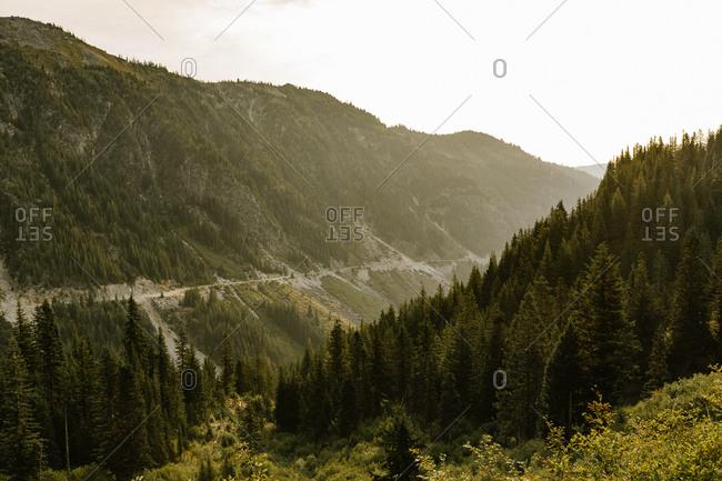 Hazy sunrise coming up over vast green mountain landscape