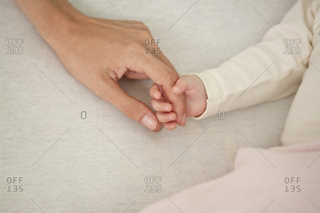 Baby holding mother's hand, cropped