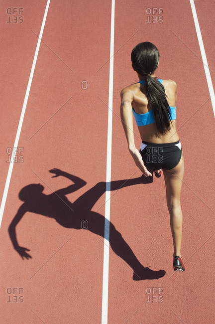 Female athlete running on track, focus on shadow