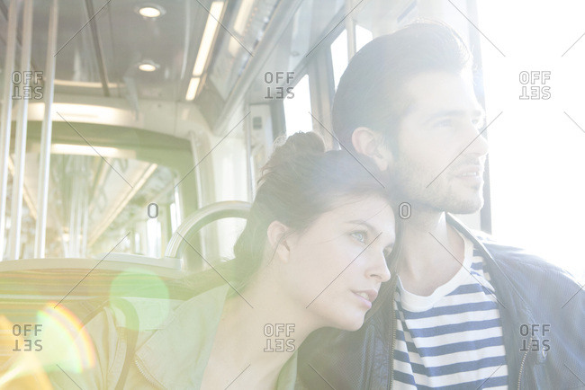 Couple riding train together, looking out window