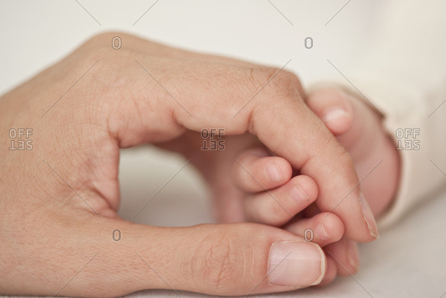 Baby and mother holding hands, cropped, close-up