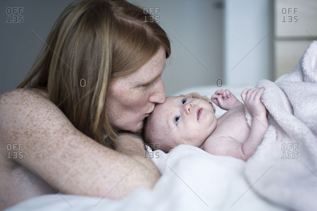Mother kissing newborn baby