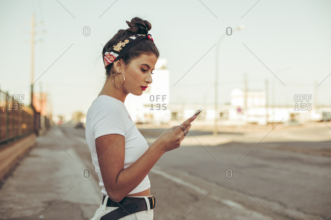 Urban portrait of a pretty brunette girl texting on her mobile phone with sunglasses during sunset