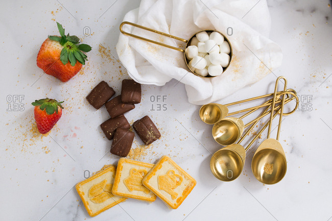 Assorted baking supplies and food on white marble counter