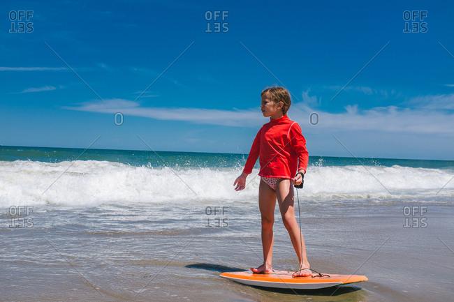 Girl standing on boogie board by ocean waves