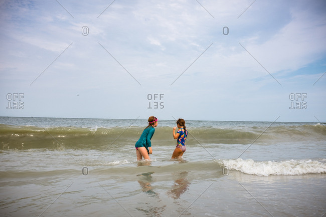 Sisters play in surf and waves at beach