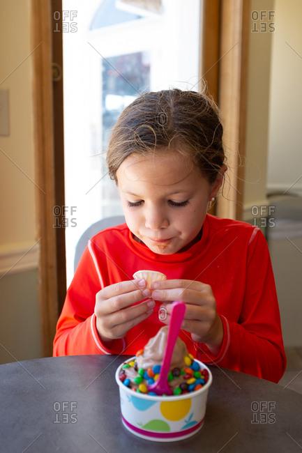 Girl eats a frozen yogurt sundae wearing orange shirt