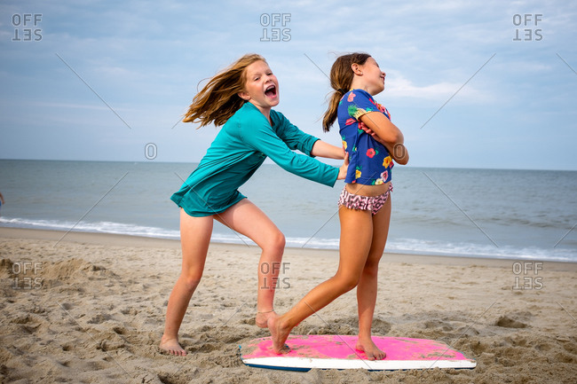 Two girls play and push each other on the beach