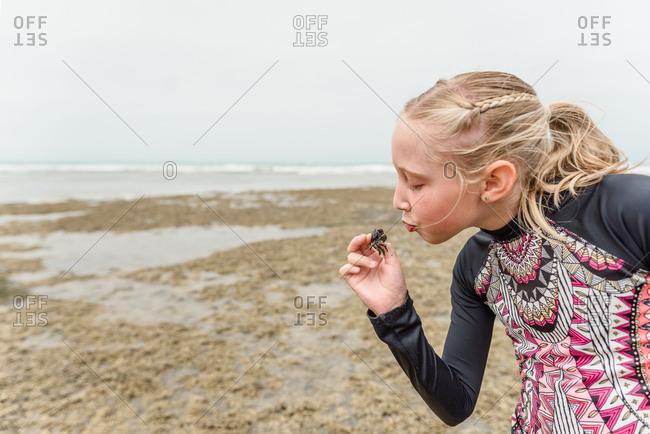 Little girl pretending to kiss a grab on the beach