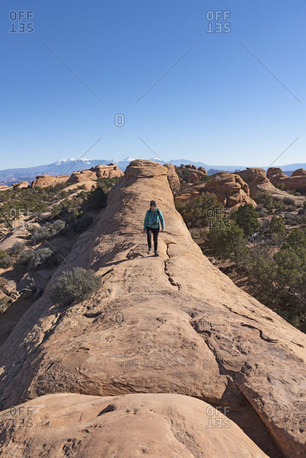 Woman hiking on rock in Arches National Park, Utah, USA