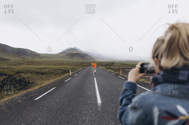Young woman photographing boyfriend walking on highway in Iceland