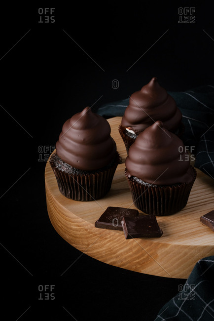Chocolate cupcakes on wooden cutting board