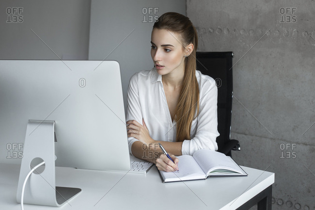 Young businesswoman taking notes while working at desktop computer