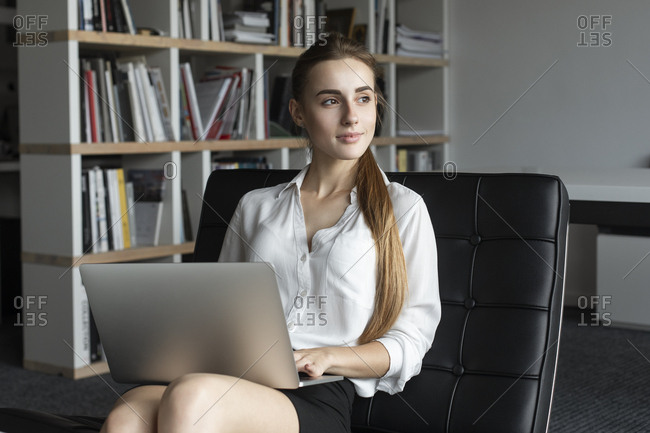 Young businesswoman working with laptop on sofa