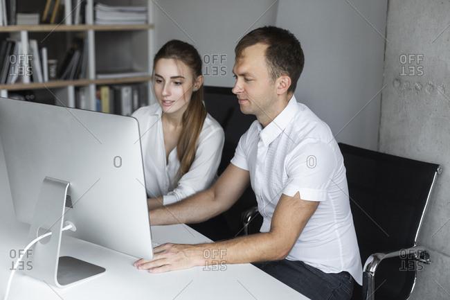 Coworkers working together at desktop computer