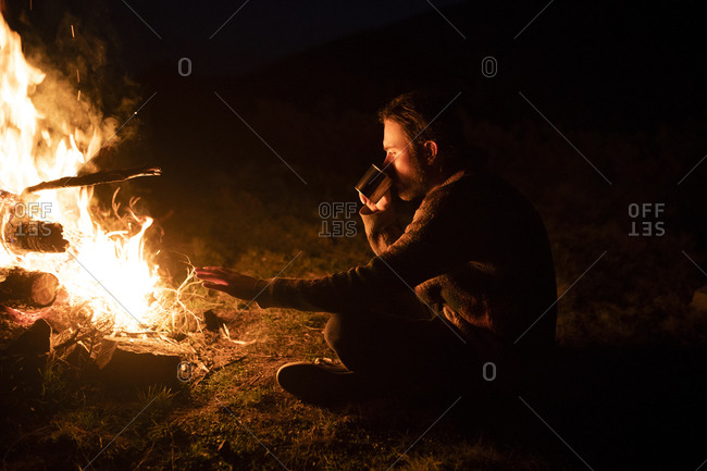 Man drinking by campfire