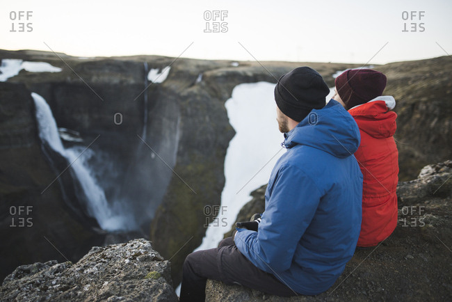 Hiker couple sitting on cliff by Haifoss waterfall in Iceland