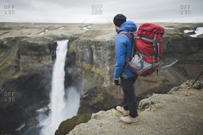 Hiker with backpack on cliff by Haifoss waterfall in Iceland