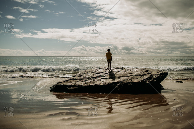 Boy standing on a rock formation surrounded by crashing waves
