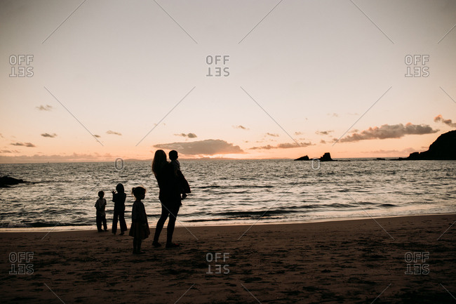 Mom standing with children on the beach at sunset
